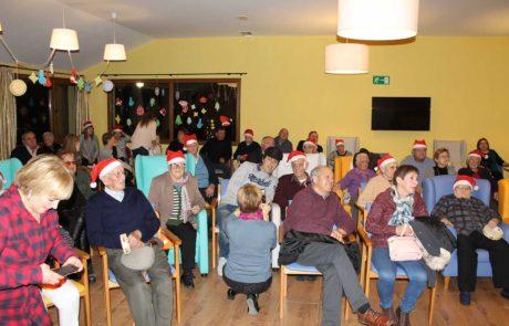 Residentes y familiares disfrutando de actuación navideña